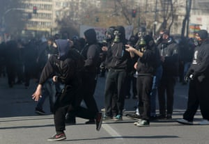 Masked protesters throw rocks at policemen following an anti-austerity march during a 24-hour strike in Athens February 20, 2013.