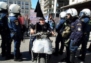 An elderly protester drives his vespa through a riot policemen barrier during a demonstration in central Athens, Greece, 20 February 2013.