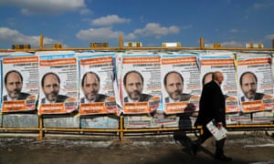 A man walks past election campaign posters in Rome, February 21, 2013.