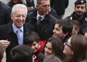 Italy's outgoing premier Mario Monti is greeted by a group of children as he arrives for his closing political rally in Florence, Italy, Friday, Feb. 22, 2013.