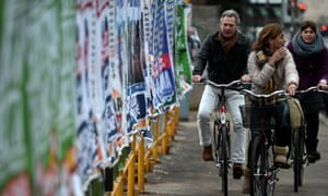 People cycle by electoral billboards in Rome on the day of campaigning. Photograph: AFP/Getty Images/Filippo Monteforte