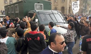 Egyptian protesters attack a police vehicle during a demonstration in Cairo
