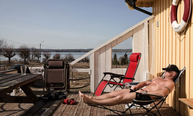 An inmate sunbathes on the deck of his bungalow on Bastoy.