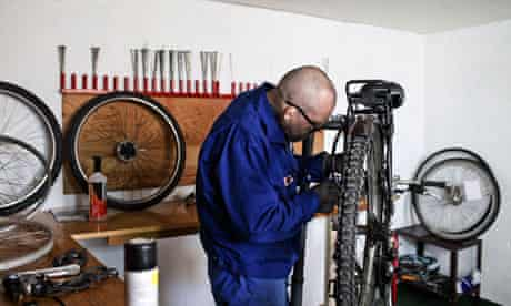 An inmate repairs a bike.