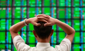 A man looks at a display board showing stock market prices inside a brokerage in Taipei