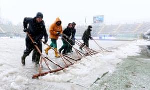 Workers remove snow from the pitch of Atleti Azzurri d'Italia stadium prior to the Italian Serie A soccer match Atalanta BC v AS Roma in Bergamo, Italy, on 24 February 2013.