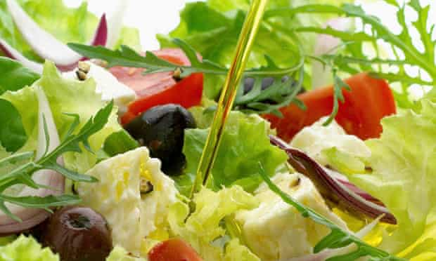 Olive oil pouring over greek salad in bowl