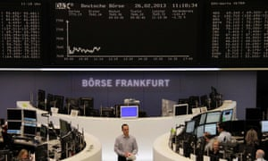 Traders are pictured at their desks in front of the DAX board at the Frankfurt stock exchange February 26, 2013.
