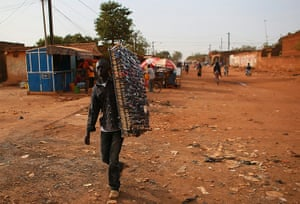 FTA: Nic Bothma: A sunglasses salesman walks down a street in Ouagadougou