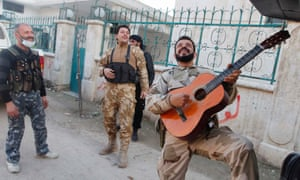 Members of the Free Syrian Army chant as one of them plays the guitar near Nairab military airport in Aleppo on Tuesday.