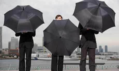 A businesswoman peeking over an umbrella