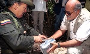 General Ernesto Gilibert, right, and Leo Arreguin, examine seized cocaine, Colombia in 2000