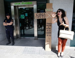 A woman shouts outside a Bankia bank branch as policemen stand guard during an anti-eviction protest in Madrid in this June last year.