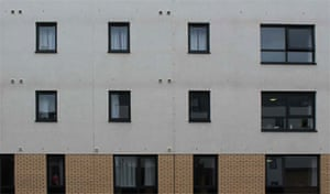 a facade of a low-value housing block with small windows