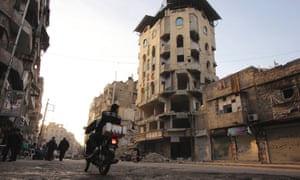 Men on a motorbike ride past the damaged al-Shifa hospital in Aleppo on Tuesday.