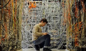 An engineer sitting in a tangle of wires