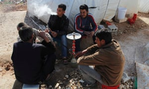 Syrian refugees smoke waterpipes outside a tent at the Bab Al-Salam refugee camp in Azaz, near the Syrian-Turkish border.