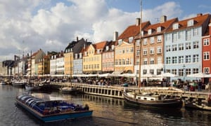 COPENHAGEN DENMARK Nyhavn, waterfront cafes bars and restaurants and tour boat on canal.