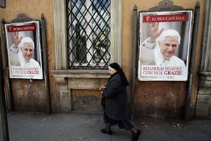 The Pope's last day: A nun walks past posters of Pope Benedict XVI
