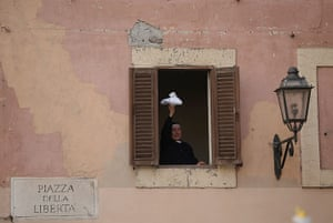 The Pope's last day: A nun waves her handkerchief as she waits for the Pope