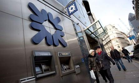 Pedestrians walk past a Royal Bank of Scotland building