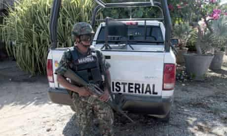 A Mexican marine stands guard outside the property in Acapulco
