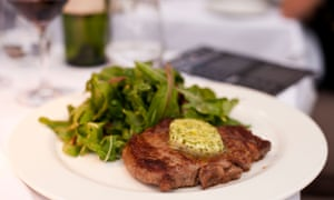 Steak served with herb butter and a green salad, with red wine in the background, on the white table linen at Gee's Restaurant.