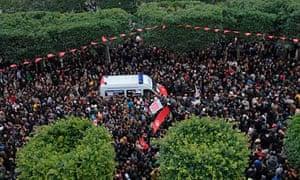 Tunisians surround an ambulance carrying the body of slain opposition leader Chokri Belaid