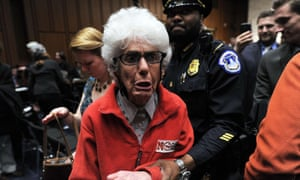 Police remove an anti-war protester as John Brennan, US President Barack Obama's pick to lead the CIA, arrives to testify before a full committee hearing on his nomination to be CIA director.