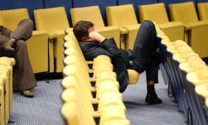 A journalist sleeps in the press room of the EU Council as European Union leaders' summit goes on through the night