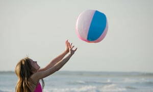 teenage girl playing volleyball with beach ball at the beach