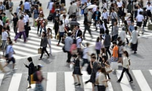 Pedestrians cross a road in front of the Shibuya station in Tokyo.