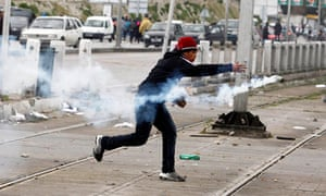 A young man throws a tear gas canister, thrown earlier by police, during clashes near the cemetery