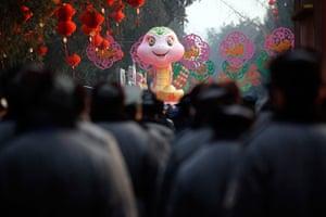 Lunar New Year: Security guards walk towards a snake sculpture in Beijing
