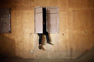 20 Photos: A Malian man sits on a window ledge to watch the African Cup of Nations