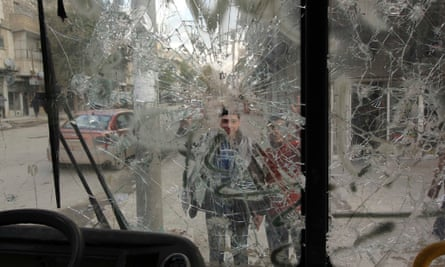 Boys are pictured through a broken windscreen as they stand on a street in Aleppo on Thursday.