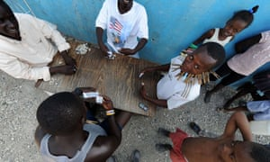 Ouch. Men play dominoes in a camp for survivors of the January 2010 quake in Port-au-Prince, Haiti. Clothes pegs are attached to the face and sometimes arms of the loser. Dominoes are played in two-person teams or with each player competing individually. Clothes pegs are one of many techniques Haitians employ to punish those who lose four games in a row.