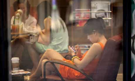 A woman looks at a smartphone in a cafe