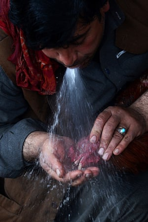 An Afghan man sprays water onto the beak of his rooster during a break in between rounds of a cock-fighting tournament in Kabul. Cockfighting is a popular game during the winter season and was banned by the Taliban rulers.