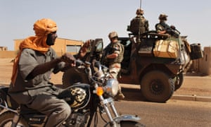 A man riding a motorcycle waves to French soldiers in an armoured vehicle in Gao, Mali. Gao has been one of the towns that has proved harder for the French as pockets of Islamist resistance remain across the north.
