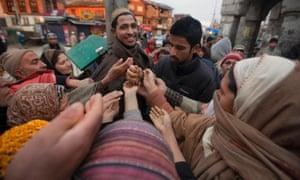 A Kashmiri Muslim man distributes raisins to devotees outside the shrine of Sufi saint Syed Abdul Qadir Jilani in Srinagar, India. Thousands of devotees thronged to the shrine which houses the relic of the saint for the yearly commemoration.