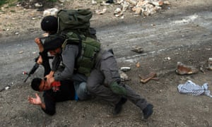 Israeli soldiers arrest a Palestinian protester during clashes at the weekly protest against the Jewish settlement of Qadomem, near Nablus, West Bank. Ten Palestinians were wounded and another four were arrested during the clashes, Palestinian sources said. Photograph: Alaa Badarneh/EPA