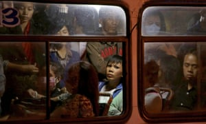 An Indonesian woman looks out from inside a crowded city bus during rush hour in Jakarta.