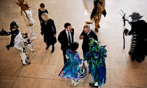 Prince Charles and Camilla chat with first year theatre design students dressed in costumes made from recycled materials for characters in the Magic Flute, at the Royal Welsh College of Music and Drama, Cardiff, Wales.