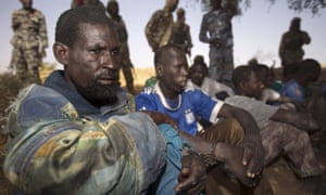 Malian soldiers guard handcuffed prisoners after they arrived by boat in Kadji, on the Niger river. French and Malian troops have launched an operation in northern Mali, where Islamists are hiding out on an island in the Niger river.