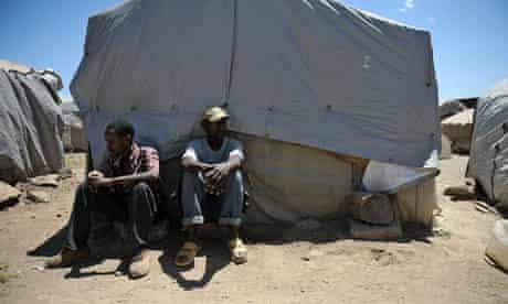 Displaced Kenyan people sit outside their makeshift shelters at Gilgil