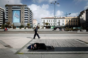 20 Photos: a pedestrian walks by as a homeless man in Omonia Square, Athens
