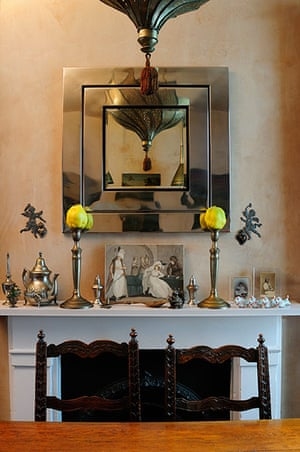 Homes - moroccan home: shot of mirror above fireplace with wooden table and chair