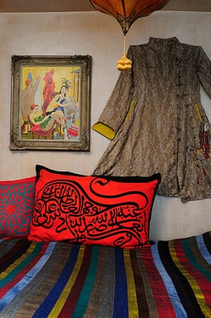 Homes - moroccan home: bed with bright red cushion and moroccan coat