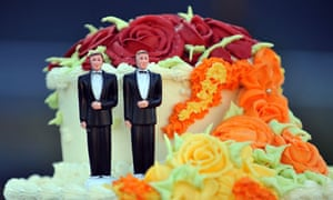 a wedding cake with two groom figurines